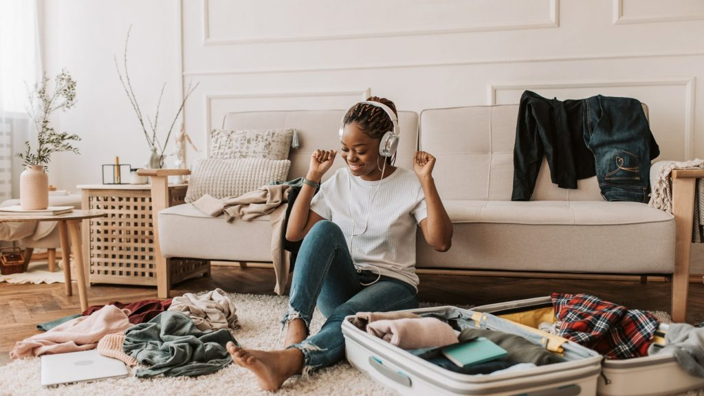 a woman listening on her headphones while packing